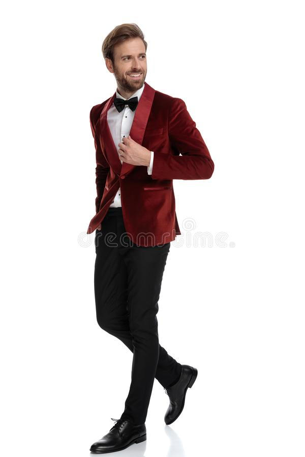 Smiling groom wearing red velvet tuxedo and walking royalty free stock photo