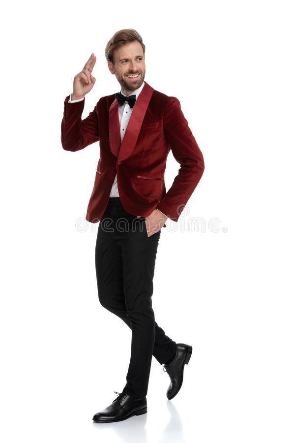 Smiling groom wearing tuxedo and military saluting stock images