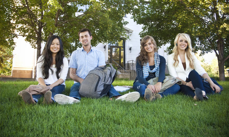 Smiling Group of Attractive Students. Young, attractive male and female students outside an academic building ready to study stock image