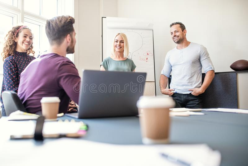 Smiling group of designers talking together after a boardroom pr stock images