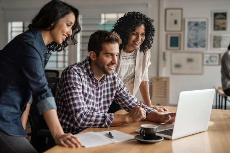 Smiling group of designers working together on an office laptop royalty free stock image