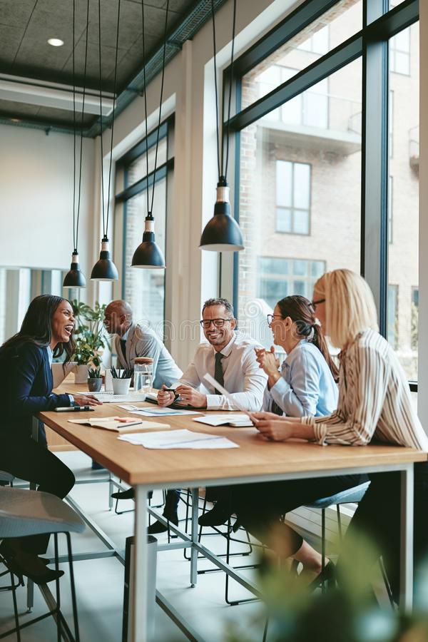 Smiling group of diverse businesspeople meeting together in an o royalty free stock images