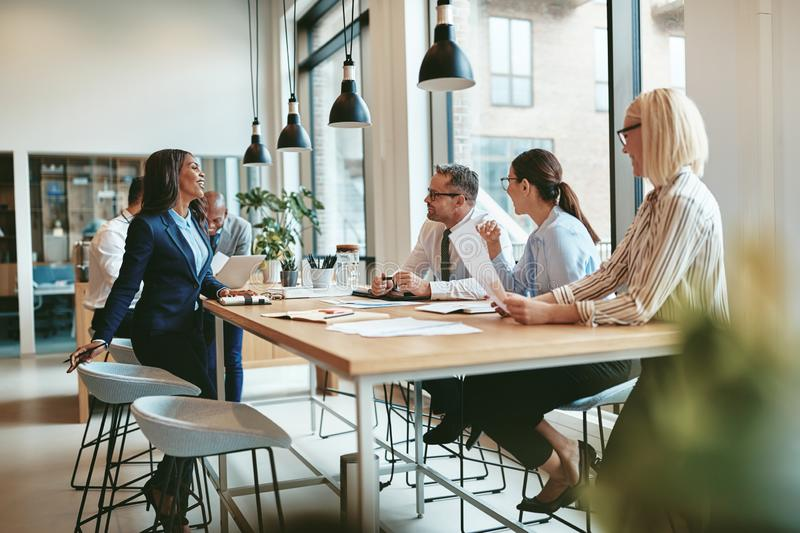 Smiling group of diverse businesspeople talking together around stock images