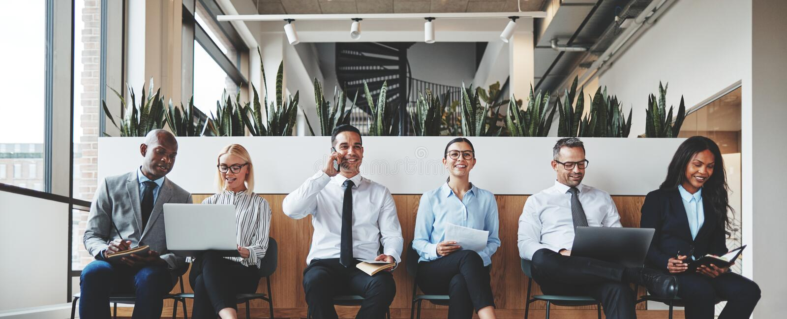 Smiling group of diverse businesspeople waiting in an office rec stock photo