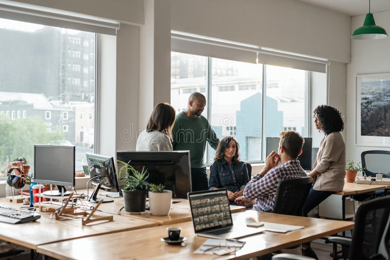 Smiling group of diverse designers meeting together in their office stock photos