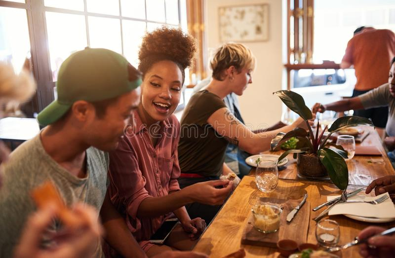 Smiling group of diverse friends talking over lunch together stock photos