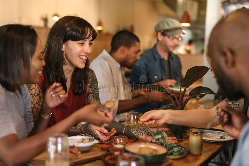 Smiling young friends enjoying dinner together in a trendy bistro royalty free stock photo