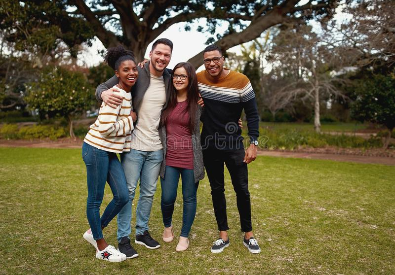 Smiling group of friends in fashionable casual clothing standing together in park outdoors smiling and very happy - royalty free stock image