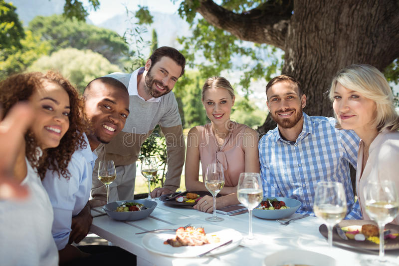 Smiling group of friends looking at camera. At restaurant royalty free stock photos