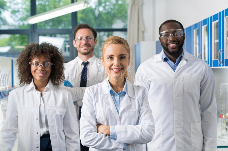 Smiling Group Of Scientists In Modern Laboratory With Female Leader, Mix Race Team Of Scientific Researchers In Lab royalty free stock photography