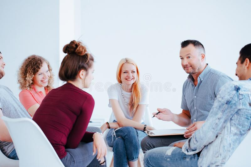 Smiling group of teenagers. During a meeting with personality coach helping them to gain self-confidence royalty free stock photography