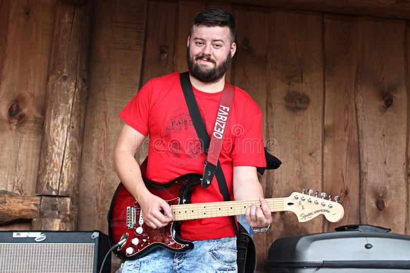 Smiling guitarist on wooden stage stock images