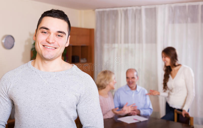 Smiling guy and big family with agent at distance indoor royalty free stock photos