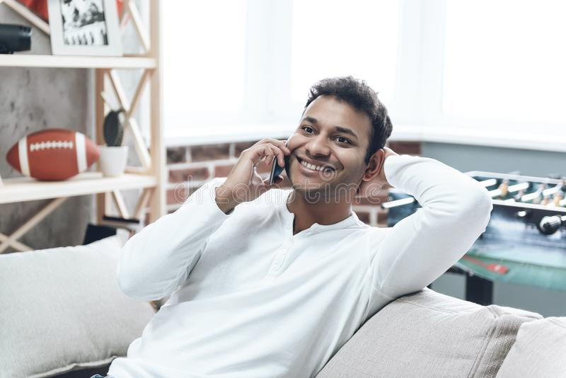 Smiling Guy in Casual Clothing using Cell Phone royalty free stock photography