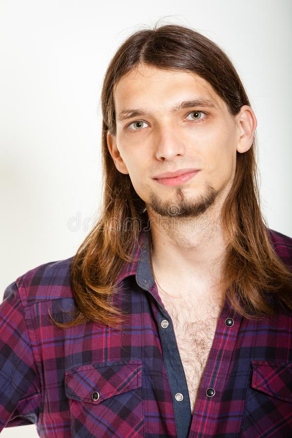 Smiling guy with long hairs. Masculinity concept. Smiling guy with long hairs. Young man in plaid shirt royalty free stock photo