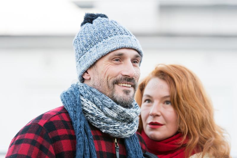 Smiling guy and rude hair woman. Portrait of lovely aged couple in city. Styled aged couple likes winter. royalty free stock photos