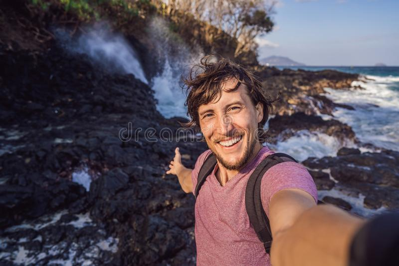 Smiling guy in the sea spray on the rocks stock photography
