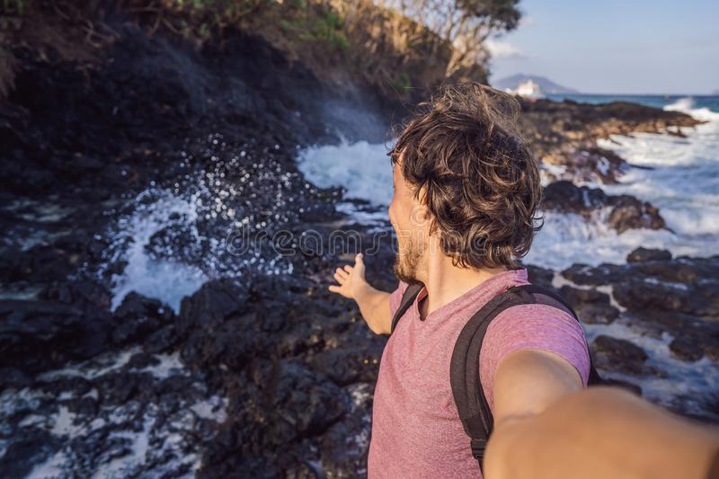 Smiling guy in the sea spray on the rocks stock image