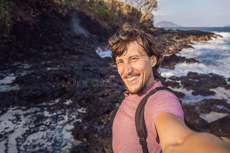 Smiling guy in the sea spray on the rocks royalty free stock image
