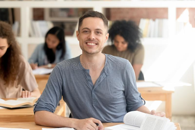 Smiling guy sitting at desk in classroom looking at camera. Diverse students gain knowledge in university busy at lecture, focus on fellow sitting on foreground stock images