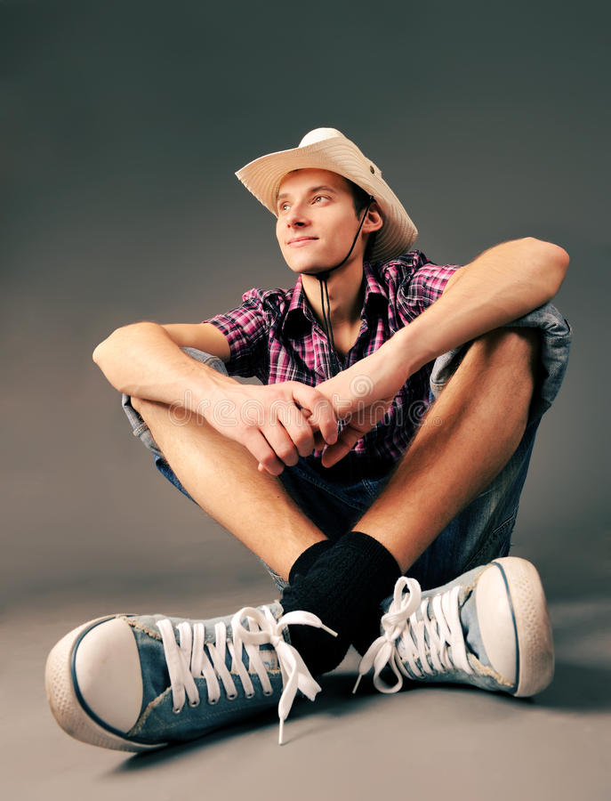 Smiling guy in sneakers and hat royalty free stock photography