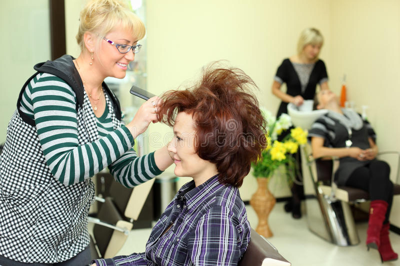Smiling hairdresser makes hair styling for woman stock photography