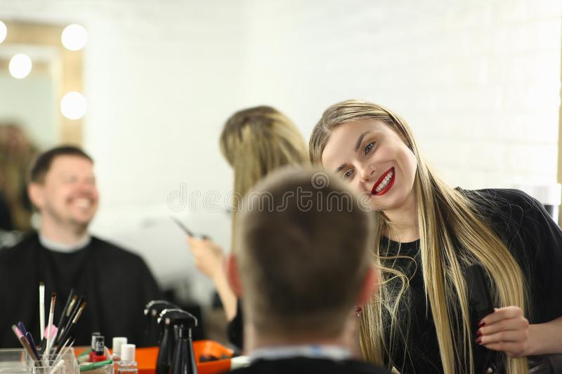 Smiling Hairstylist Making Haircut for Male Client. Woman Barber Styling Hairdo for Man in Barbershop. Hairdresser with Hairbrush in Hand Doing Hairstyle for stock photo