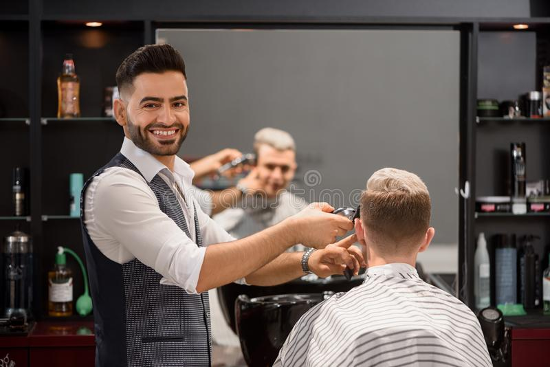 Smiling barber trimming client`s stylish haircut and looking at camera. royalty free stock photos