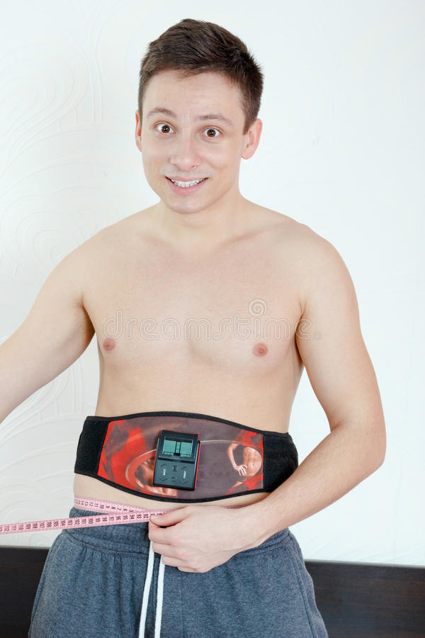 Smiling Half-naked handsome young man with an electrical device stock images