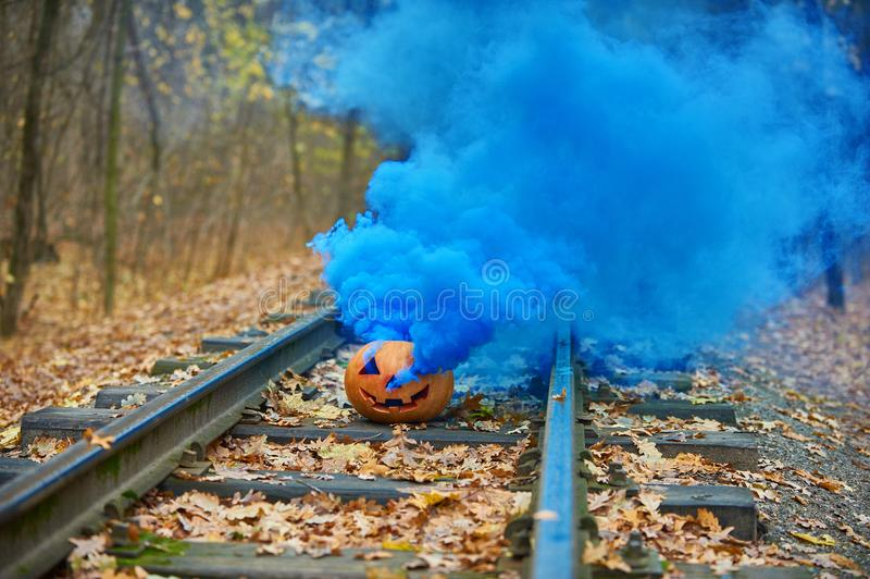 Smiling halloween pumpkin with bright blue smoke on the rails in the forest. Selective focus royalty free stock images