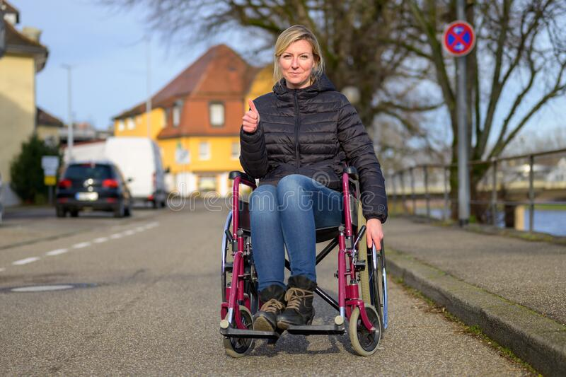 Smiling handicapped woman using a wheelchair. In an urban street giving a thumbs up to show her positive attitude stock photo