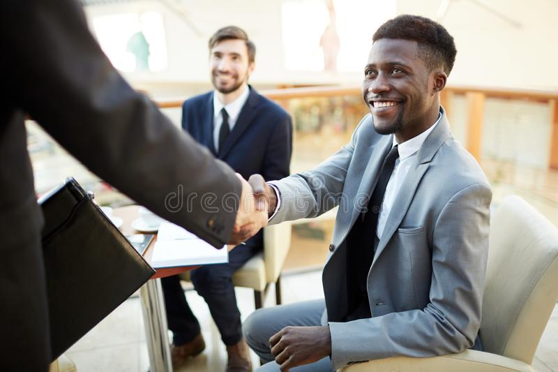 Greeting new business partner. Smiling handsome Afro-American businessman with beard sitting in armchair and making handshake with new business partner while stock photos