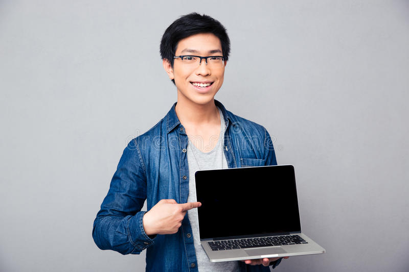 Smiling handsome asian man showing on laptop screen. Smiling handsome asian man showing finger on laptop screen. Looking at camera royalty free stock photos