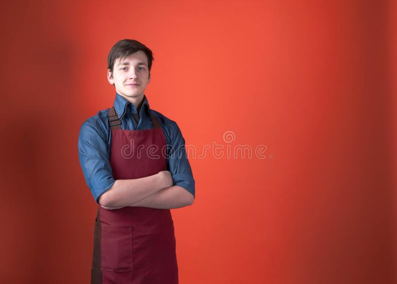 Smiling handsome barista with dark hair in burgundy apron looking at camera with crossed arms royalty free stock photos