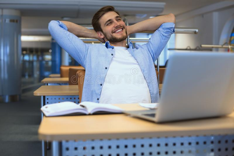 Smiling handsome businessman relaxing in a modern office royalty free stock image