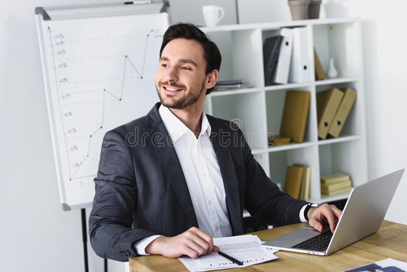 smiling handsome businessman sitting at table and looking away stock photo