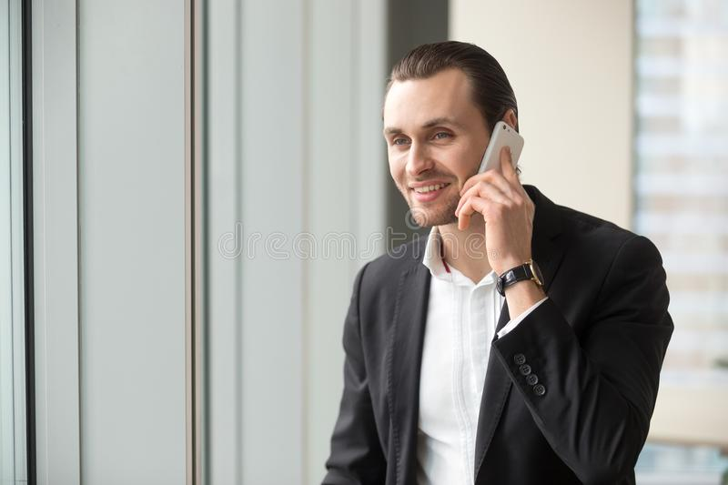 Smiling handsome businessman in suit talking on cellphone. royalty free stock images