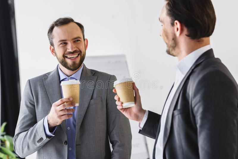 smiling handsome businessmen drinking coffee at coffee break stock images