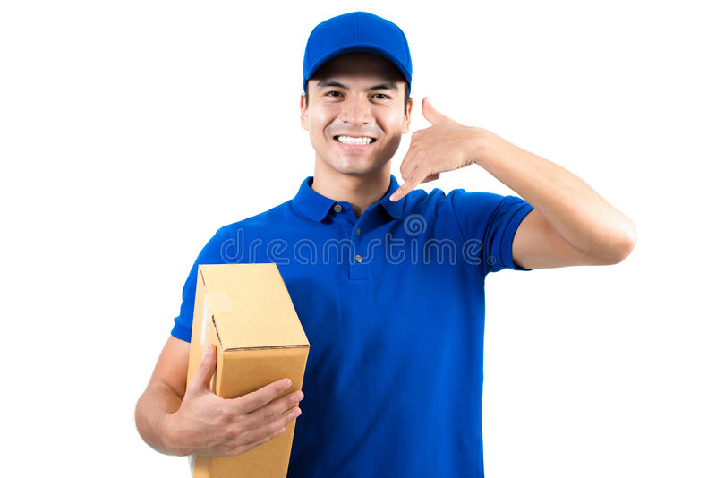 Smiling handsome delivery man holding box and making call me gesture royalty free stock photography