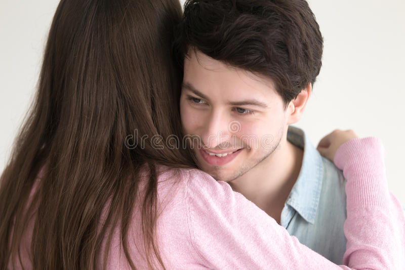 Smiling handsome guy embracing young lady, couple hugging on dat stock photo