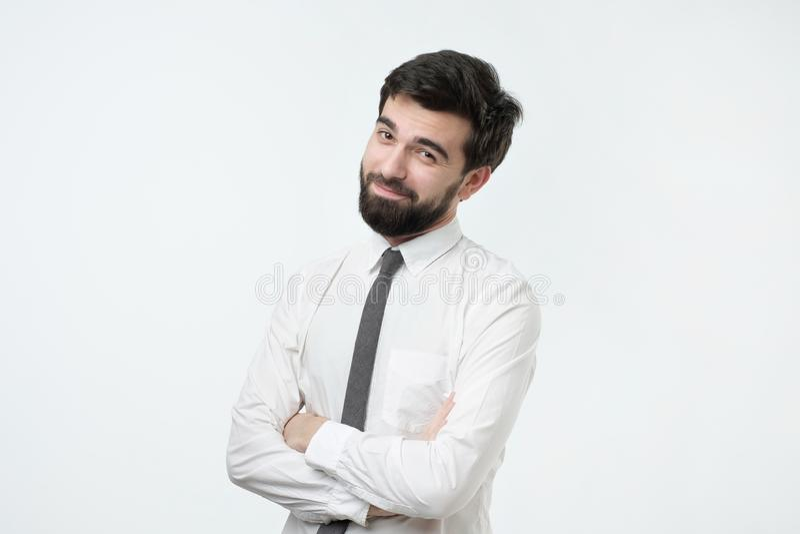 Smiling handsome hispanic man in white shirt crossing hands. Smiling handsome hispanic man with black beard in white shirt crossing hands royalty free stock photo