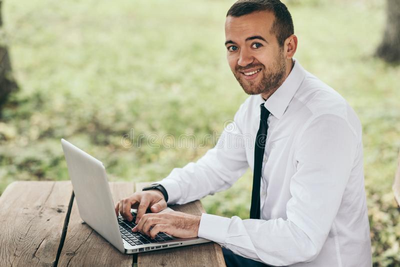 Smiling handsome male in white shirt sitting at wood table using laptop having pleased sincere smile while surfing on Internet. royalty free stock images