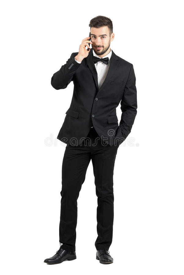 Smiling handsome man in formal wear talking on the smartphone looking at camera royalty free stock images