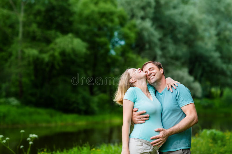 Smiling handsome man hugging her beautiful young pregnant woman royalty free stock images