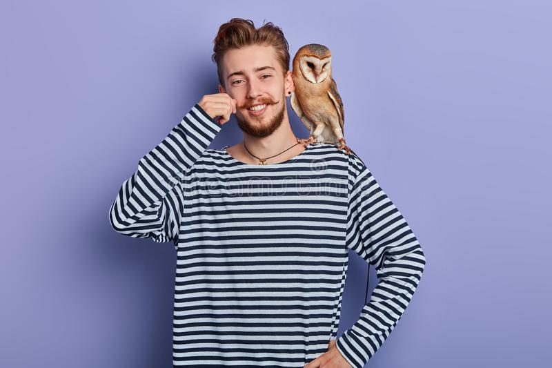 Smiling handsome man with an owl sitting on his shoulder. stock photography