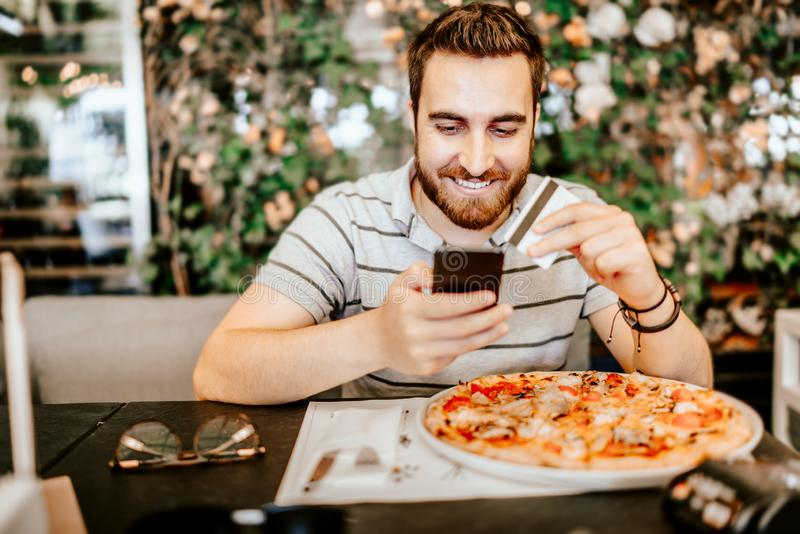 Smiling handsome man paying at restaurant using smartphone and mobile paying technology with credit card stock photo
