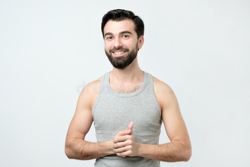 Smiling handsome man in singlet standing smiling royalty free stock photography