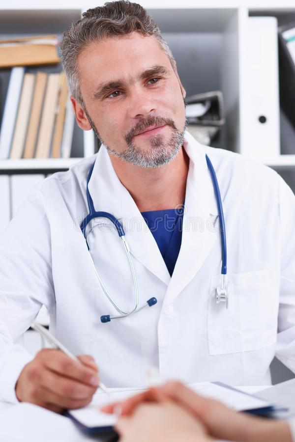 Smiling handsome mature doctor communicate with patient royalty free stock image