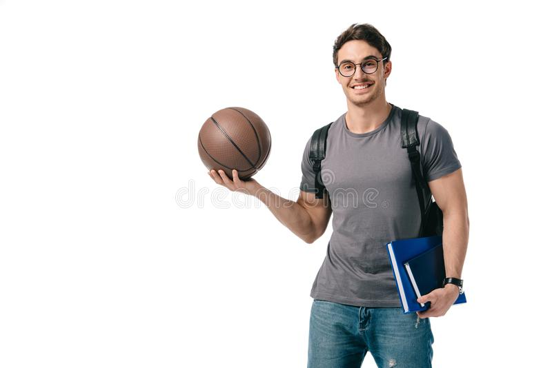 Smiling handsome student holding basketball ball. Isolated on white stock photos