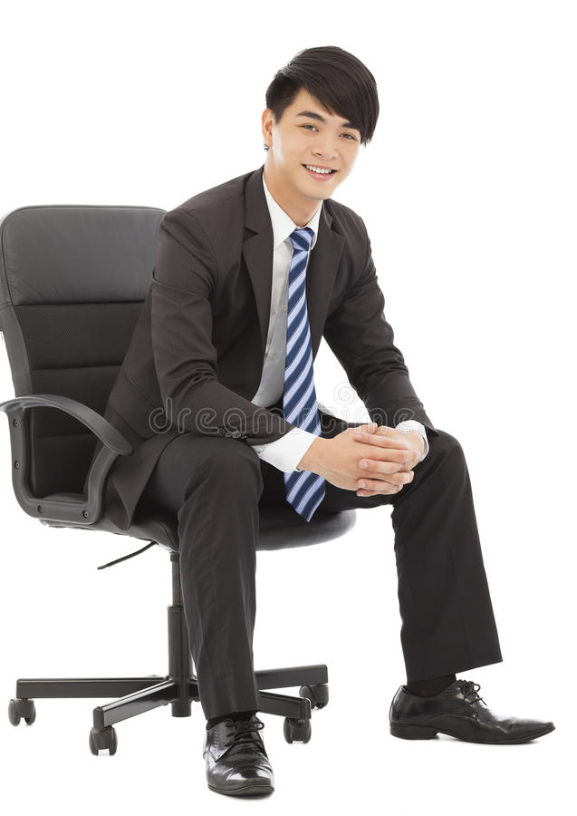 Smiling and handsome Young business man sitting on a chair royalty free stock image